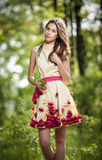 Young beautiful girl in a yellow dress in the woods. Portrait of romantic woman in fairy forest. Stunning fashionable teenager. Young beautiful girl in a yellow stock photography