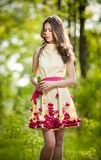 Young beautiful girl in a yellow dress in the woods. Portrait of romantic woman in fairy forest. Stunning fashionable teenager Royalty Free Stock Image