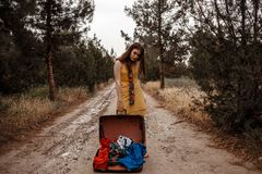 Young beautiful girl in a yellow vintage dress posing on a muddy country road with an open retro suitcase in her hands.  stock photos