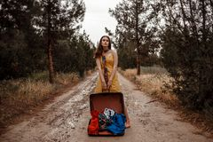 Young beautiful girl in a yellow vintage dress posing on a muddy country road with an open retro suitcase in her hands.  royalty free stock image