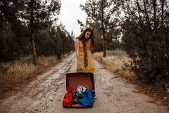 Young beautiful girl in a yellow vintage dress posing on a muddy country road with an open retro suitcase in her hands.  royalty free stock photo