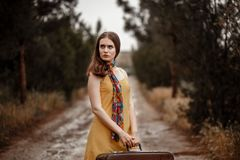 Young beautiful girl in a yellow vintage dress posing on a muddy country road with a retro suitcase in hand.  stock images