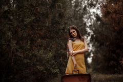 Young beautiful girl in a yellow vintage dress posing on a muddy country road with a retro suitcase in hand.  royalty free stock photo