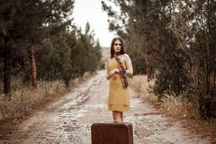 Young beautiful girl in a yellow vintage dress posing on a muddy country road with a retro suitcase in hand.  stock photos