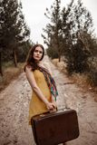 Young beautiful girl in a yellow vintage dress posing on a muddy country road with a retro suitcase in hand.  royalty free stock photos