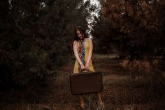 Young beautiful girl in a yellow vintage dress posing on a muddy country road with a retro suitcase in hand. Young beautiful girl in a yellow vintage dress stock image