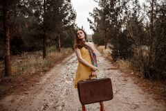 Young beautiful girl in a yellow vintage dress posing on a muddy country road with a retro suitcase in her hands.  royalty free stock images