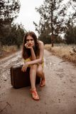Young beautiful girl in a yellow vintage dress posing on a muddy country road, sitting on a retro suitcase.  royalty free stock images