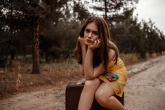 Young beautiful girl in a yellow vintage dress posing on a muddy country road, sitting on a retro suitcase.  royalty free stock photo