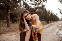 Young beautiful girl in a yellow vintage dress posing on a muddy country road, sitting on a retro suitcase.  royalty free stock photos