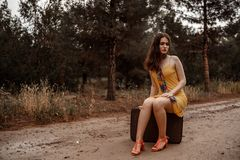 Young beautiful girl in a yellow vintage dress posing on a muddy country road, sitting on a retro suitcase.  stock photos