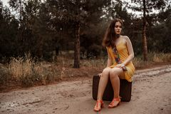 Young beautiful girl in a yellow vintage dress posing on a muddy country road, sitting on a retro suitcase.  royalty free stock image