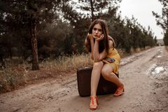 Young beautiful girl in a yellow vintage dress posing on a muddy country road, sitting on a retro suitcase.  stock photo