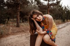Young beautiful girl in a yellow vintage dress posing on a muddy country road, sitting on a retro suitcase.  stock photography