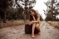 Young beautiful girl in a yellow vintage dress posing on a muddy country road, sitting on a retro suitcase.  stock image