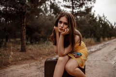 Young beautiful girl in a yellow vintage dress posing on a muddy country road, sitting on a retro suitcase.  royalty free stock photography