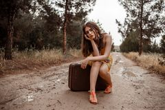 Young beautiful girl in a yellow vintage dress posing on a muddy country road, sitting on a retro suitcase.  stock images