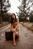 Young beautiful girl in a yellow vintage dress sitting on a retro suitcase on a muddy country road.  royalty free stock image