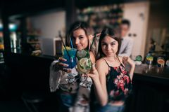 Young beautiful girls with cocktails near the bar stock photography