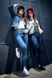 Young beautiful girls with denim suit in a urban background Stock Photos