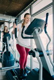 Young beautiful girls exercising in the gym with ski machine royalty free stock images