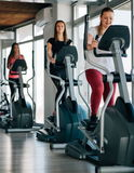 Young beautiful girls exercising in the gym with ski machine stock images