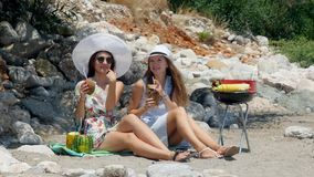 Young beautiful girls in hat and sunglasses drinking fresh coconut cocktails while talking and smiling on the sand beach. Young beautiful girls in sunglasses stock footage