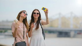 Young beautiful girls having fun and making selfie. Concept of friendship and fun with new trends and technology. Best. Portrait of two young positive woman stock video footage