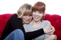 Young beautiful girls hug while sitting Stock Photo