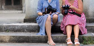 Young beautiful girls photographers in striped dresses stock photography