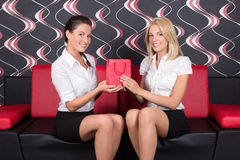 Young beautiful girls sitting on the sofa with present Royalty Free Stock Photo