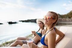 Young beautiful girls smiling, sunbathing, lying on chaises near sea. Young beautiful girls smiling, sunbathing, holding glasses with juice, lying on chaises Royalty Free Stock Photos