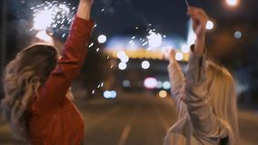 Young beautiful girls with sparklers dancing happily with their hands up to music in the night city. Slow motion stock video footage