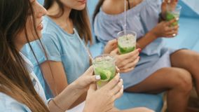 Young beautiful girls on summer vacations drinking mojito at beach bar. Young beautiful girls students on summer vacations drinking mojito at beach bar. Summer stock footage