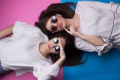 Young girls having fun. Young beautiful girls with sunglasses having fun isolated on pink and blue backgorund Royalty Free Stock Photography