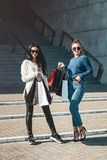 Beautiful girls with paper bags outside shopping mall. Young beautiful girls in sunglasses with paper bags walking out of shopping mall. Building on a background stock photo