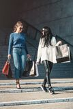 Beautiful girls with paper bags outside shopping mall. Young beautiful girls in sunglasses with paper bags walking out of shopping mall. Building on a background stock photos
