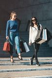 Beautiful girls with paper bags outside shopping mall. Young beautiful girls in sunglasses with paper bags walking out of shopping mall. Building on a background stock images