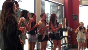 Young beautiful girls taking picture. Inside Starbucks store stock footage