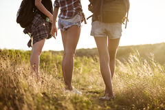 Young beautiful girls travelers walking in canyon at sunset. Royalty Free Stock Images
