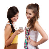 Young beautiful girls using the cellphone to send and receive sms Royalty Free Stock Photo