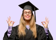 Young beautiful graduate woman student. Young woman university graduate student doing ok sign gesture with both hands expressing meditation and relaxation Stock Image