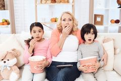 Young beautiful grandmother with her grandchildren eating popcorn and watching movie at home on couch. stock images