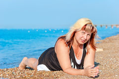 Young beautiful grandmother resting on the beach Royalty Free Stock Image