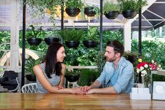 Young beautiful guy girl white cafe green leaves happy couple relaxing summer cafe love story communication. Man and women on a date in a cafe hold hands. Happy Royalty Free Stock Image