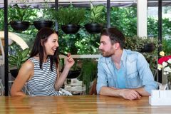 Young beautiful guy girl white cafe green leaves happy couple relaxing summer cafe love story communication. Man and women on a date in a cafe hold hands. Happy Royalty Free Stock Photo