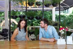 Young beautiful guy girl white cafe green leaves happy couple relaxing summer cafe love story communication. Man and women on a date in a cafe hold hands. Happy Stock Image