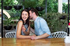 Young beautiful guy girl white cafe green leaves happy couple relaxing summer cafe love story communication. Man and women on a date in a cafe hold hands. Happy Stock Images
