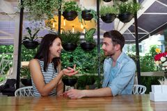 Young beautiful guy girl white cafe green leaves happy couple relaxing summer cafe love story communication. Man and women on a date in a cafe hold hands. Happy Stock Photos