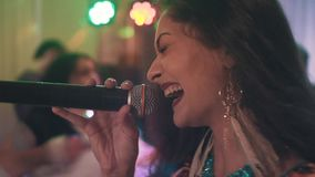Young beautiful Gypsy with dark hair and beautiful earrings emotionally singing into the microphone. Musical event stock footage
